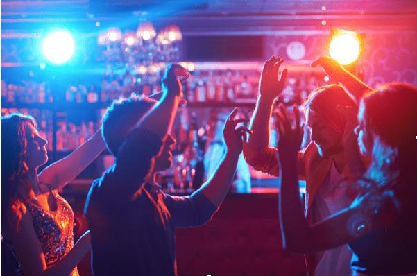 Vier Freunde tanzen auf einer Party vor einer Bar
